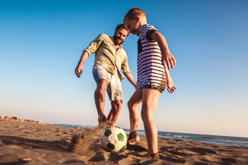 Ojciec i syn bawić się piłkę nożną lub futbol na plaży ma wielkiego rodzinnego czas na wakacjach letnich obraz stock