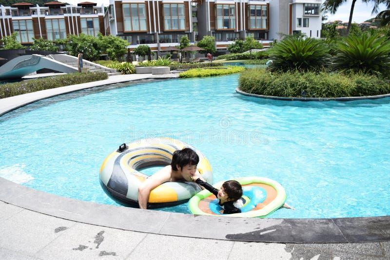 ojciec i syn bawić się przy lato basenem zdjęcia royalty free
