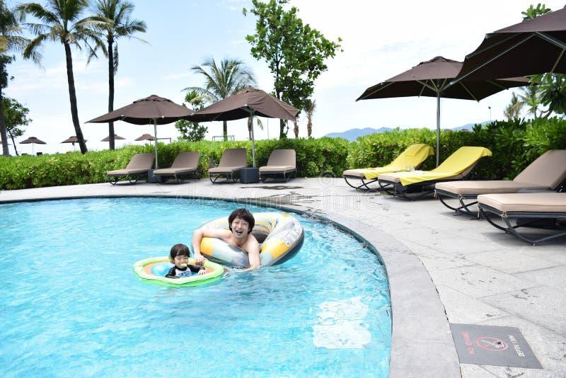 ojciec i syn bawić się przy lato basenem zdjęcia stock