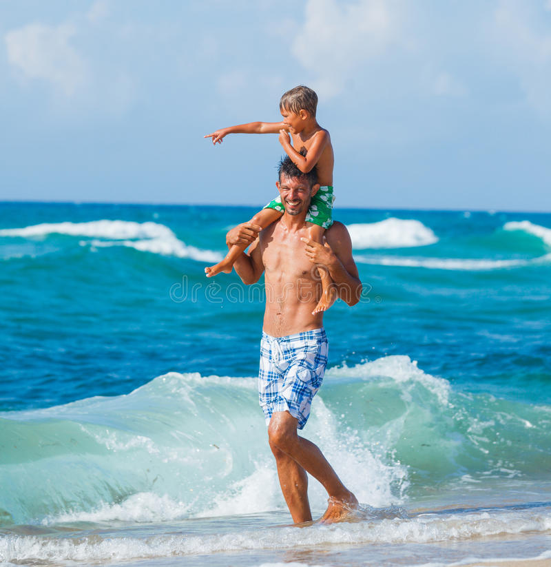 Ojciec i syn bawić się w morzu obrazy stock