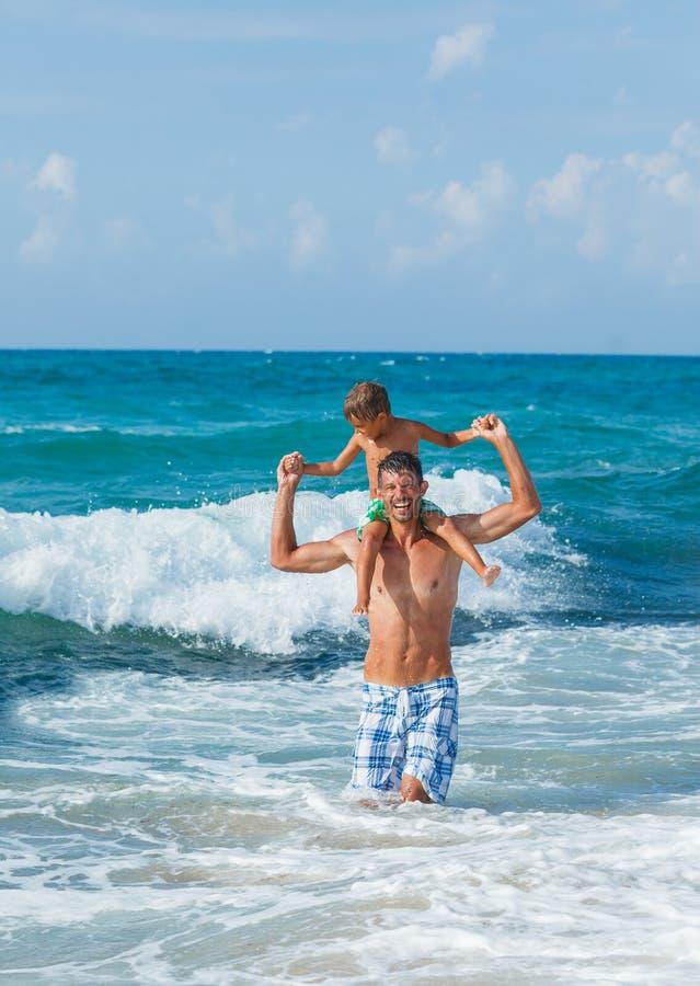 Ojciec i syn bawić się w morzu zdjęcia royalty free