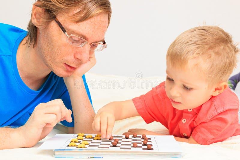 Ojciec i syn bawić się warcabów obrazy stock