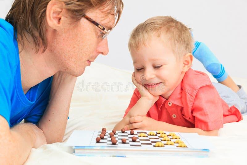 Ojciec i syn bawić się warcabów zdjęcia stock