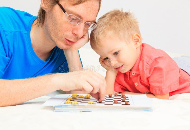 Ojciec i syn bawić się warcabów zdjęcia royalty free