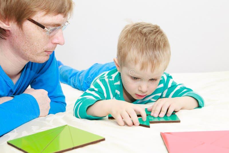 Ojciec i syn bawić się z łamigłówką obrazy royalty free
