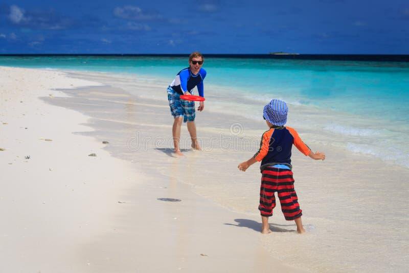Ojciec i syn bawić się z latającym dyskiem przy plażą obrazy royalty free
