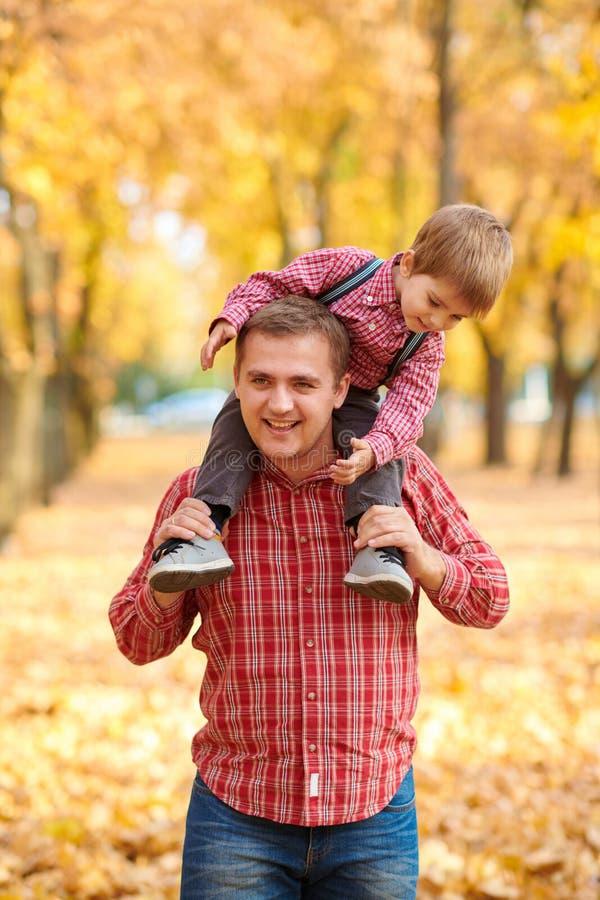 Ojciec i syn bawić się zabawę i mamy w jesieni miasta parku One pozuje, ono uśmiecha się, bawić się Jaskrawi żółci drzewa zdjęcie royalty free