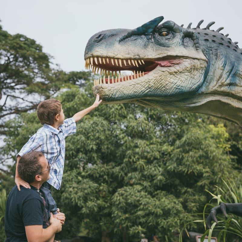 Ojciec i syn bawi? si? w przygody Dino parku obraz royalty free