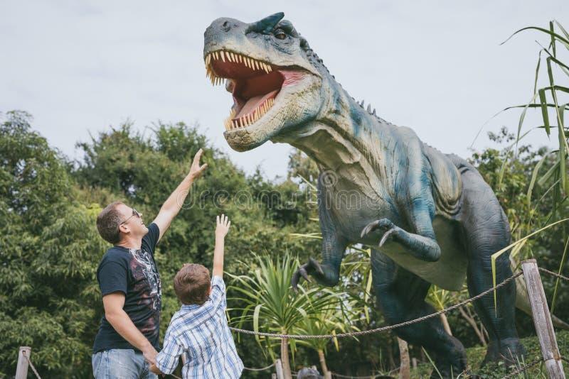 Ojciec i syn bawi? si? w przygody Dino parku zdjęcia royalty free