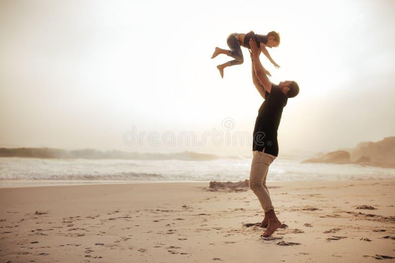 Ojciec i syn cieszy się wakacje przy dennym brzeg obrazy royalty free