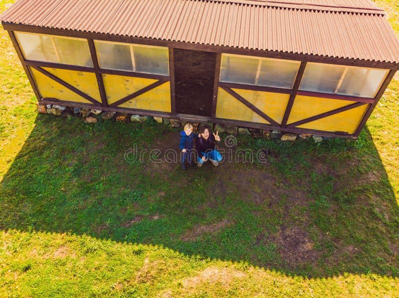 Ojciec i syn działa trutnia pilotem do tv Młody człowiek z chłopiec latającym trutniem, cieszy się wakacje fotografia royalty free