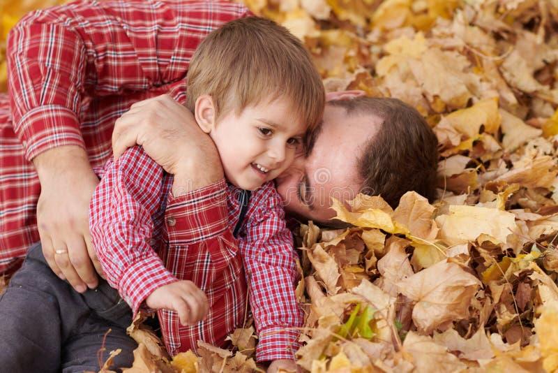 Ojciec i syn kłamamy na żółtych liściach i mamy zabawę w jesieni miasta parku One pozuje, ono uśmiecha się, bawić się Jaskrawi żó zdjęcia stock
