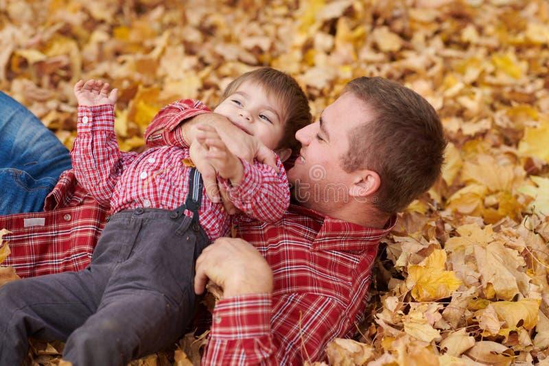 Ojciec i syn kłamamy na żółtych liściach i mamy zabawę w jesieni miasta parku One pozuje, ono uśmiecha się, bawić się Jaskrawi żó obrazy royalty free