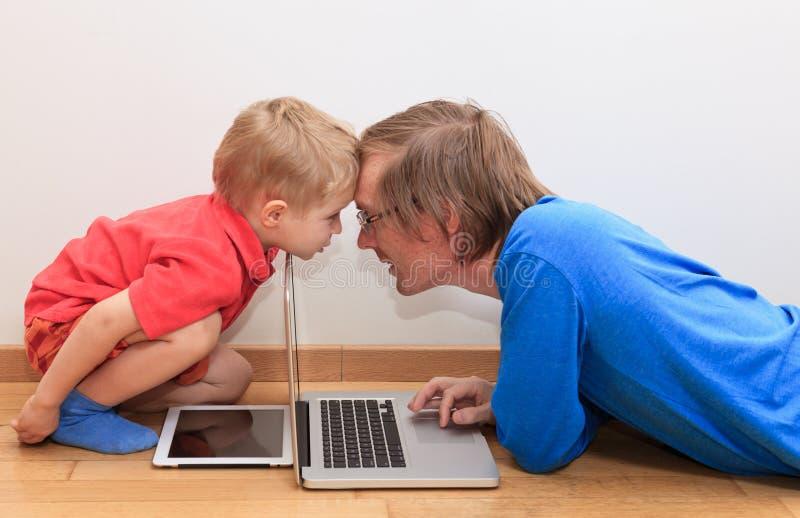 Ojciec i syn kolidujemy nad dotyka komputerem i ochraniaczem zdjęcia royalty free