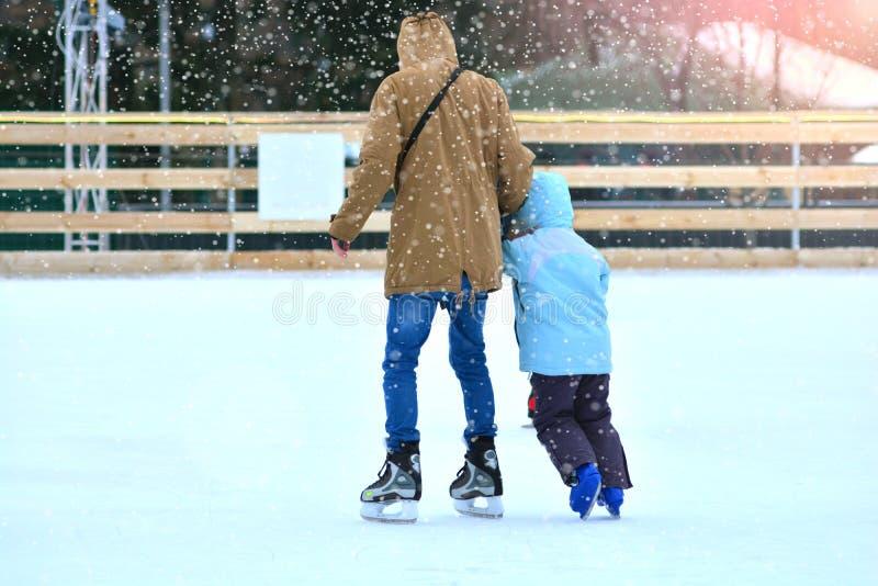 Ojciec i syn na łyżwiarskim lodowisku Tata trenuje jego syna jeździć na łyżwach kiting rzeczna narciarska śnieżna sport zima obrazy royalty free