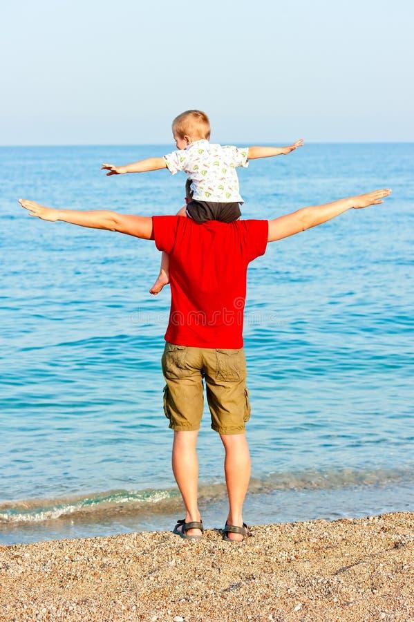 Ojciec i syn na plaży przedstawiamy lot obrazy royalty free