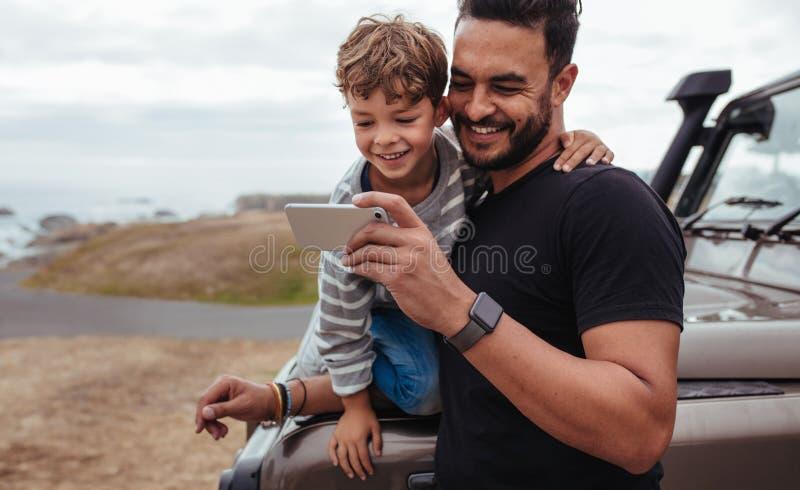 Ojciec i syn na wycieczce samochodowej używać mądrze telefon obrazy royalty free