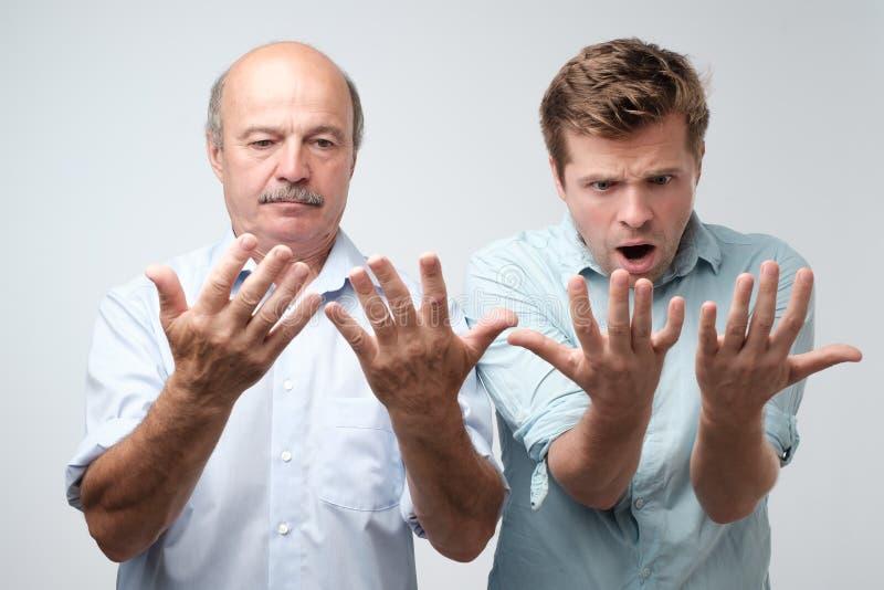 Ojciec i syn patrzeje ich palmy z szokiem fotografia stock