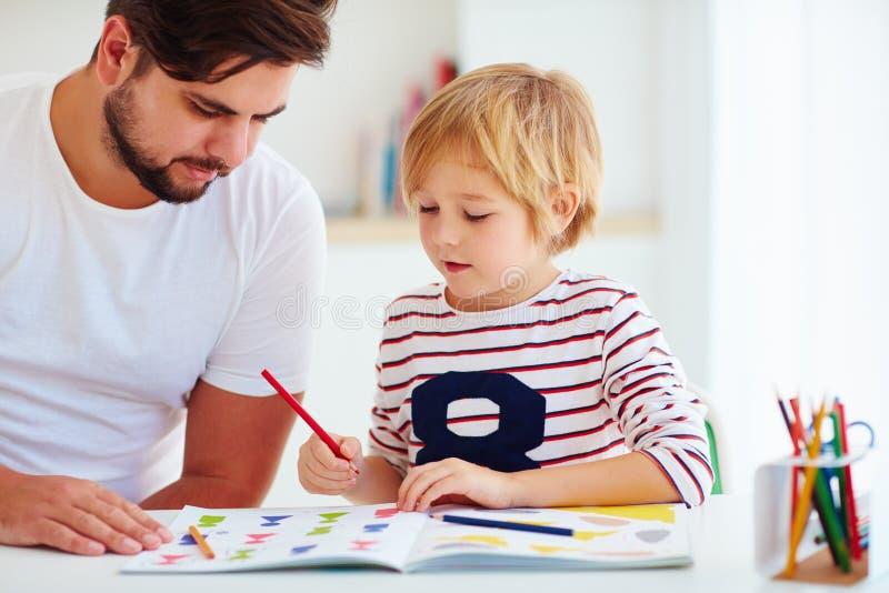 Ojciec i syn przy biurkiem, kształci w domu zdjęcie stock