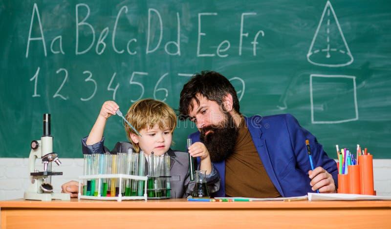 Ojciec i syn przy szkołą tylna szko?y używać mikroskop w lab uczeń robi nauka eksperymentom z mikroskopem wewnątrz zdjęcie stock