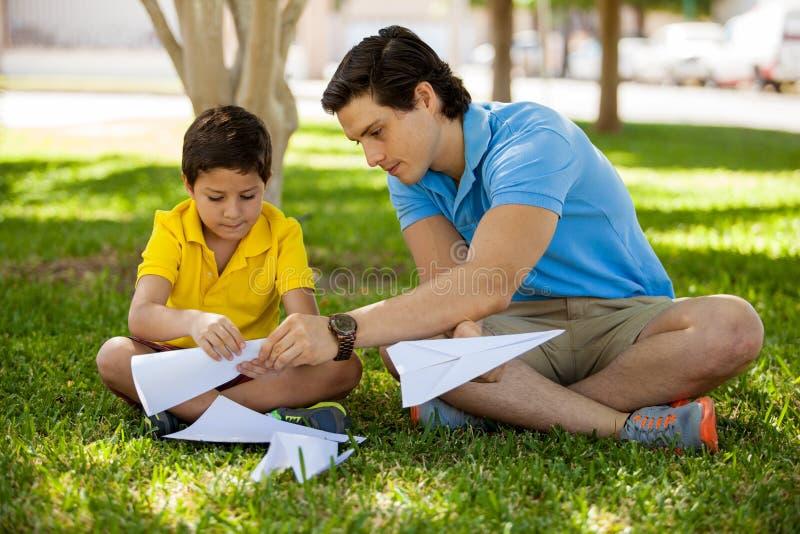 Ojciec i syn robi papierów samolotom zdjęcia royalty free