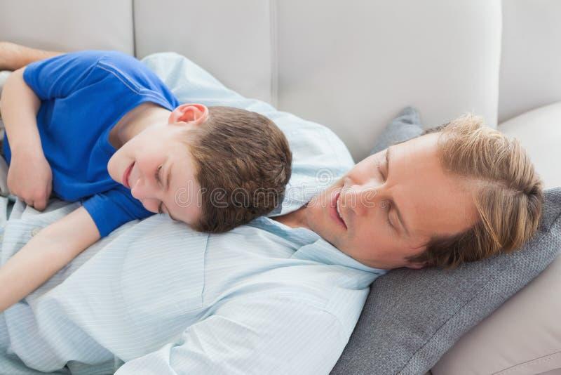 Ojciec i syn używa drzemanie na leżance zdjęcie stock