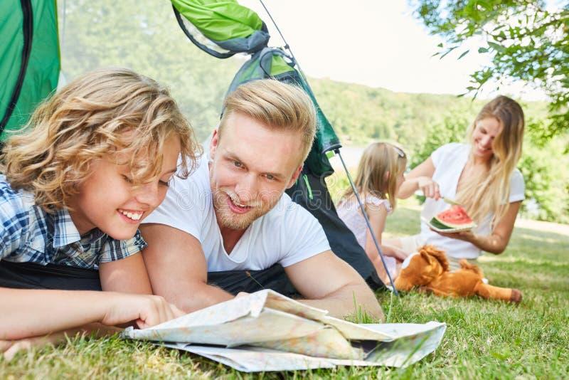 Ojciec i syn w namiotowym spojrzeniu na mapie zdjęcie royalty free