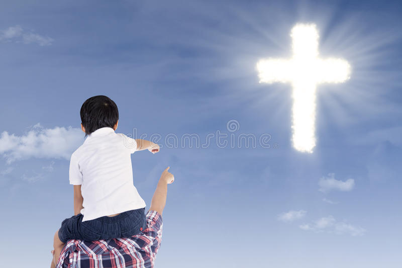 Ojciec i syn wskazuje przy krzyżem obrazy stock