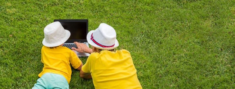 Ojciec i syn z notatnikiem na pogodnym letnim dniu Nowy podejście edukacja Tylny widok dwa chłopiec z laptopu lying on the beach  obrazy royalty free