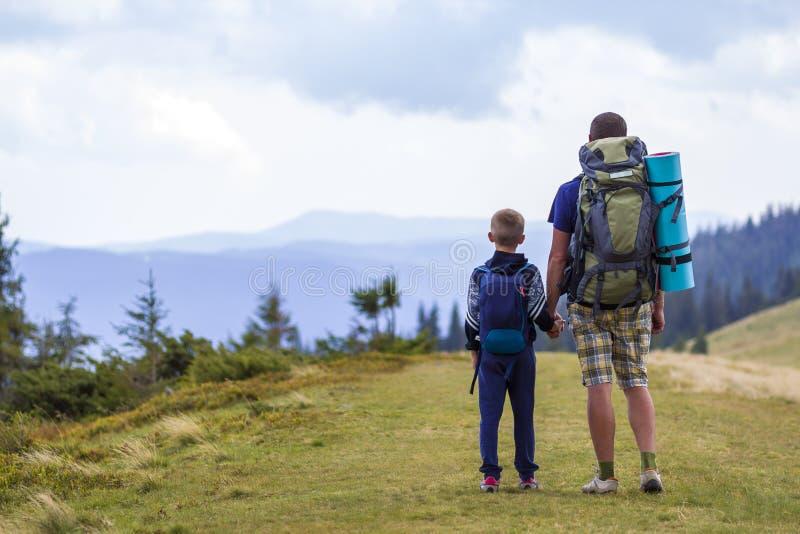 Ojciec i syn z plecakami wycieczkuje wpólnie w scenicznych lato zieleni górach Tata i dziecka pozycja cieszy się krajobrazową gór zdjęcia stock