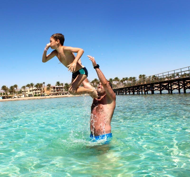Ojciec i syn zabawę przy morzem obraz stock