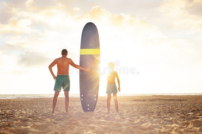 Ojciec i syn zachodu słońca stoją na pokładzie surfingu na morzu fotografia royalty free