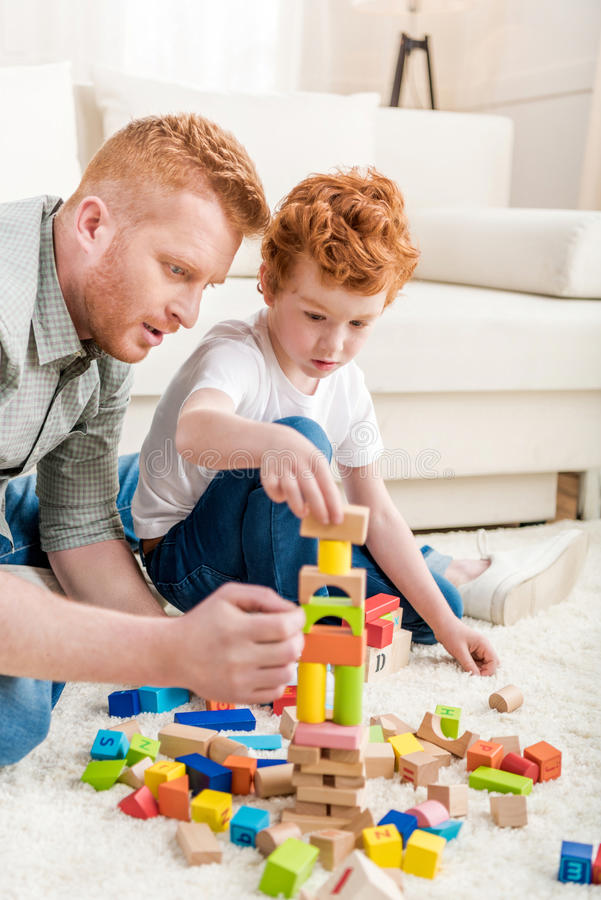 Ojciec i uroczy syn bawić się z konstruktorem na podłoga w domu zdjęcie royalty free