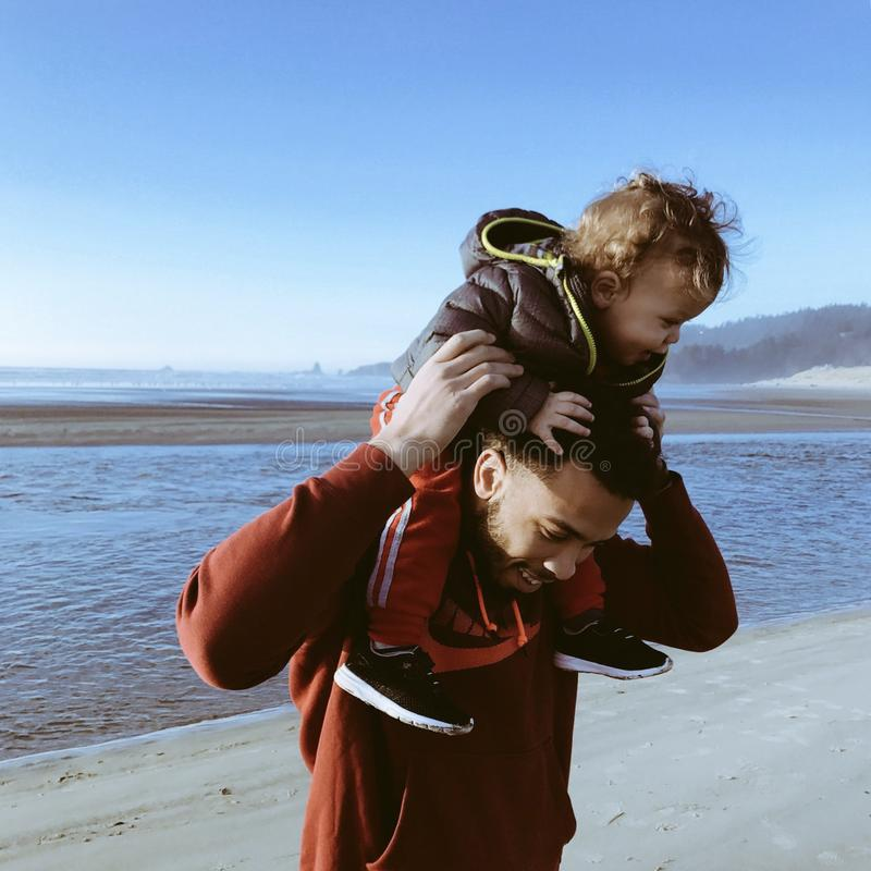 Ojciec niesie jego syna na plaży