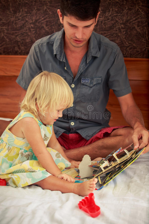 ojciec pokazuje dziecięcą książkę mały blondynki daughte obraz stock