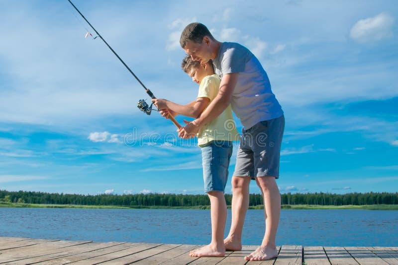 Ojciec pokazuje jego syna na molu dlaczego trzymać połowu prącie łapać ryby, przeciw błękitnemu niebu i jezioru obraz royalty free
