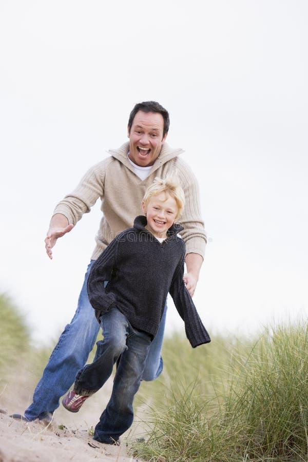 ojciec prowadzi uśmiechniętego beach syna. obrazy royalty free