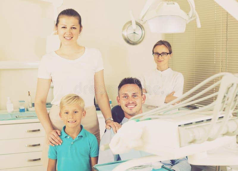 Ojciec rodzina siedzi w stomatologicznym krześle zdjęcie royalty free