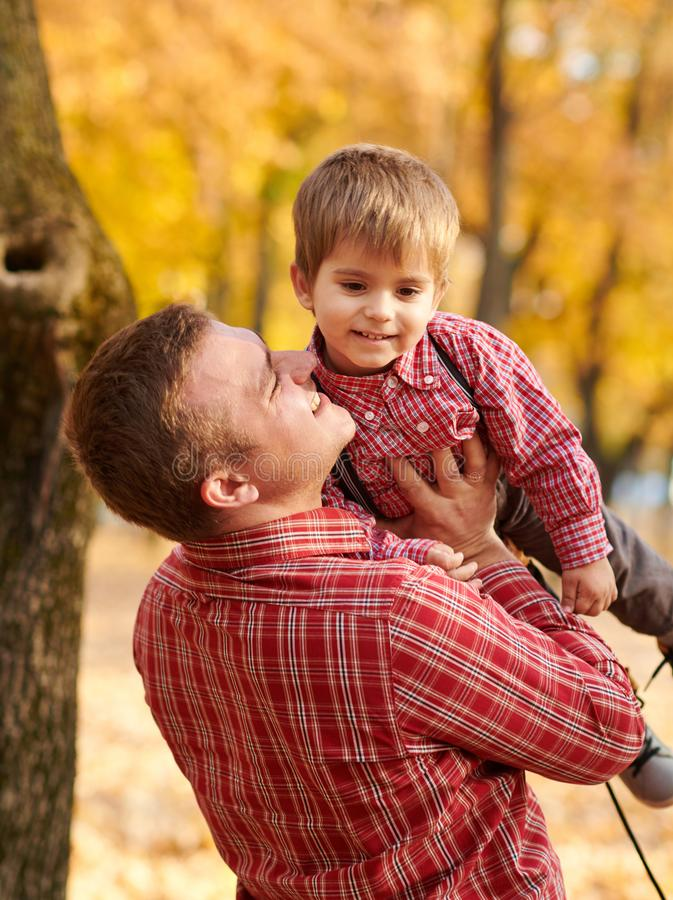 Ojciec rzuca chłopiec wysokość w górę Ojciec i syn bawić się zabawę i mamy w jesieni miasta parku One pozuje, ono uśmiecha się, b zdjęcia stock
