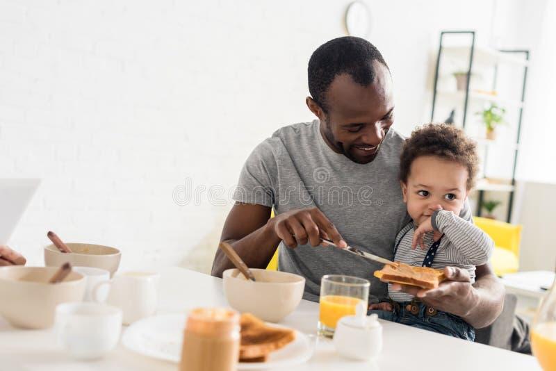 ojciec stosuje masło orzechowe na grzance fotografia royalty free