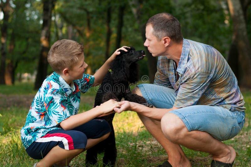 Ojciec, syn i czarny pudel, obraz stock