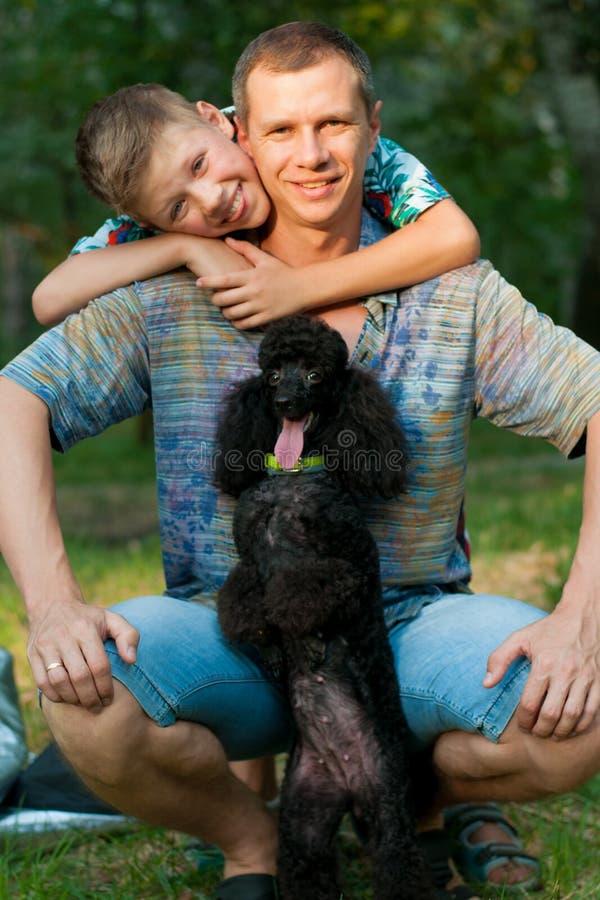 Ojciec, syn i czarny pudel, zdjęcia royalty free