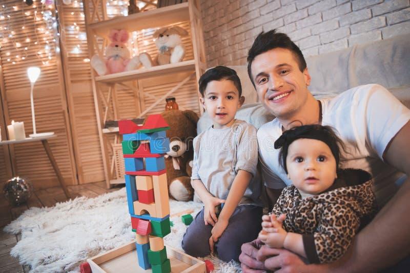 Ojciec, syn i mała dziecko córka, bawić się z sześcianami dla dzieci przy nocą w domu obrazy royalty free