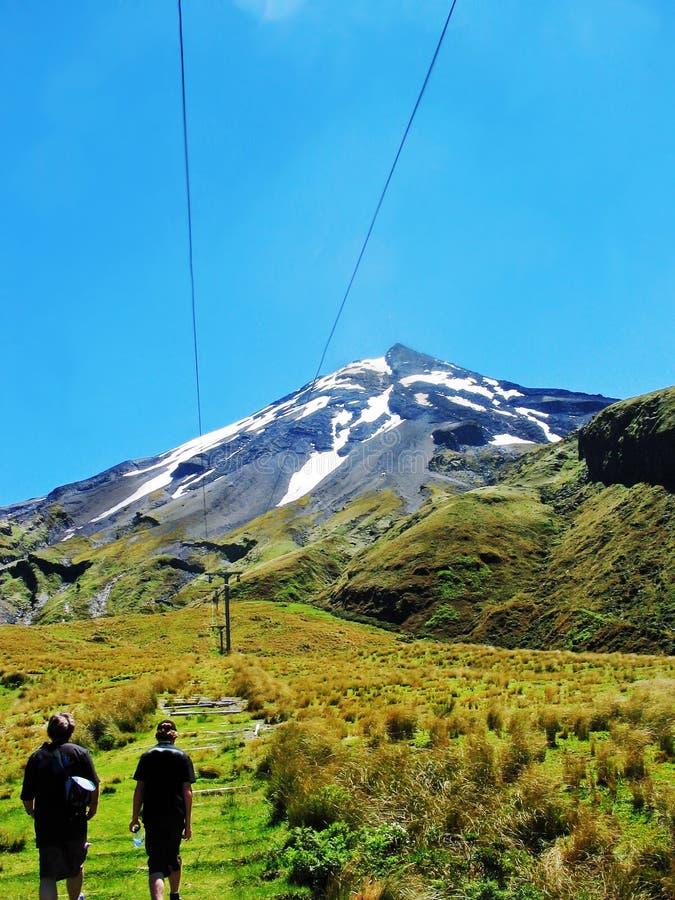 Ojciec & syn wycieczkuje up szlakowego śnieżna góra NZ fotografia royalty free