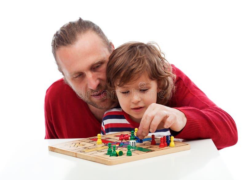 Ojciec uczy jego syna bawić się grę planszowa fotografia royalty free