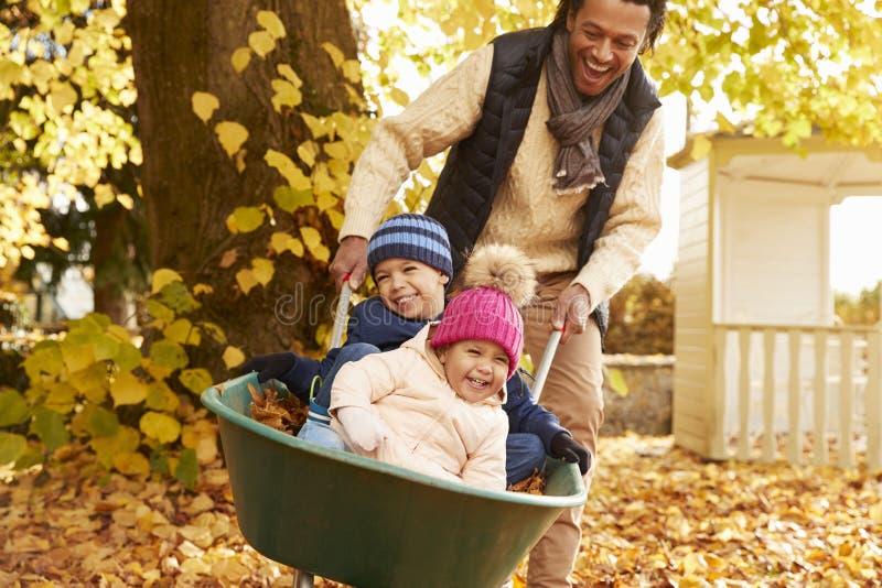 Ojciec W jesień ogródzie Daje dzieciom przejażdżce W Wheelbarrow fotografia stock