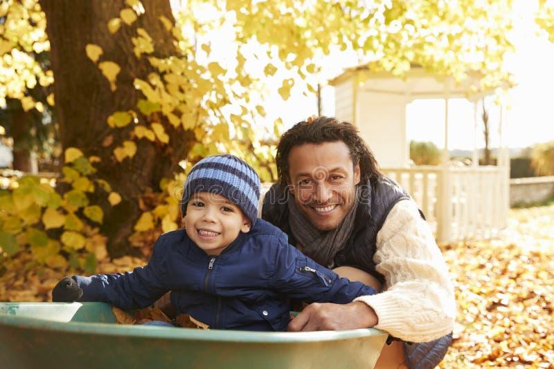 Ojciec W jesień ogródzie Daje syn przejażdżce W Wheelbarrow zdjęcia royalty free