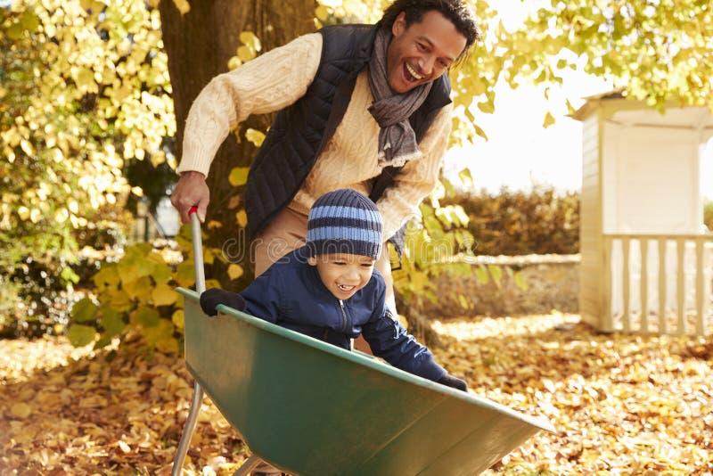 Ojciec W jesień ogródzie Daje syn przejażdżce W Wheelbarrow fotografia stock