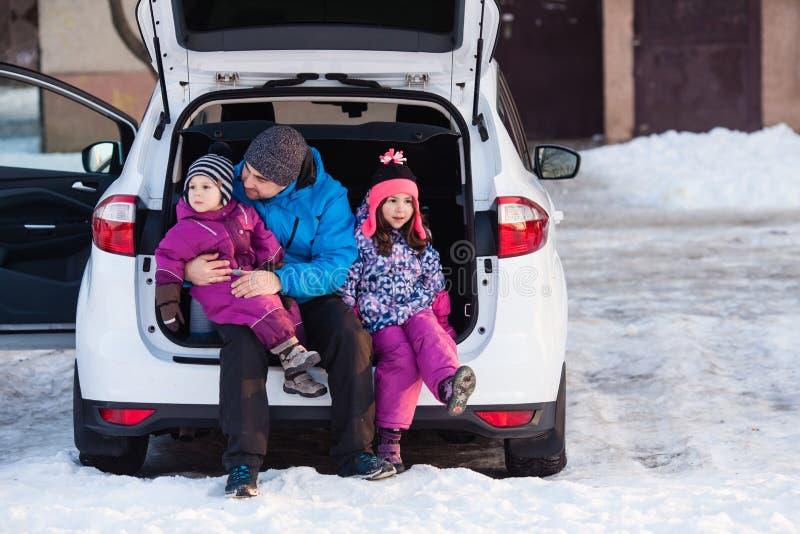 Ojciec z dzieciakami siedzi na samochodowym bagażniku zdjęcie stock