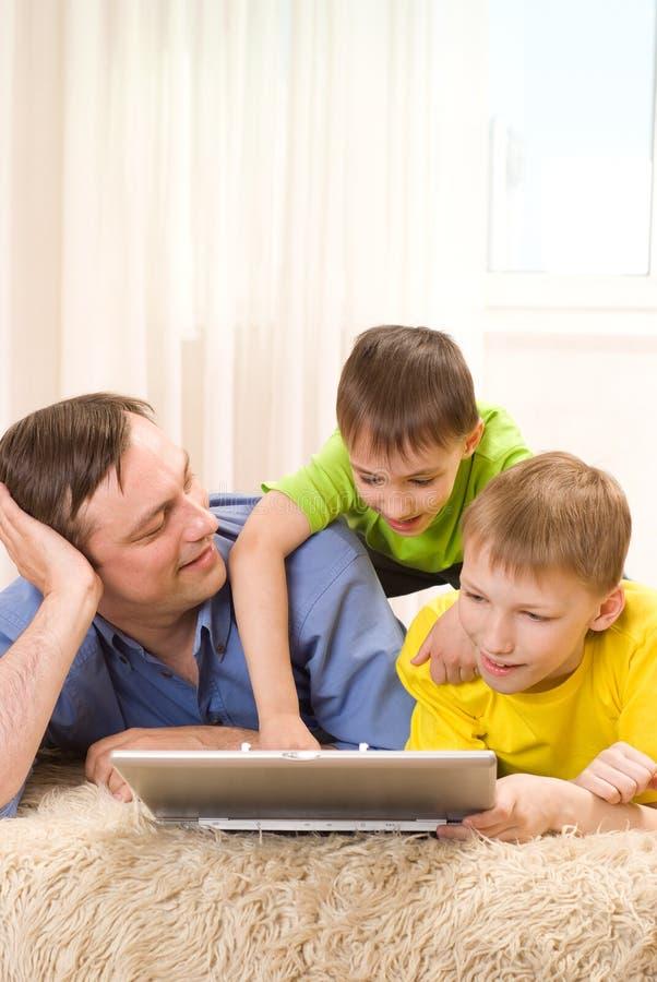 Ojciec z jego synami z laptopem fotografia stock